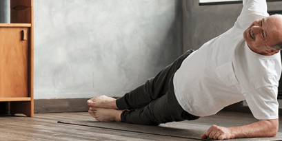 Middle-aged man living with Parkinson's disease practices yoga to help with symptoms.